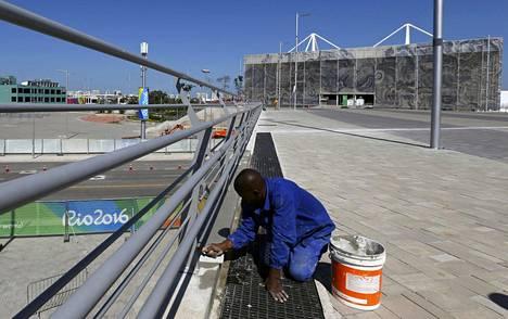 Työmies viimeisteli maanantaina olympiapuistoa. Avajaiset ovat perjantaina.