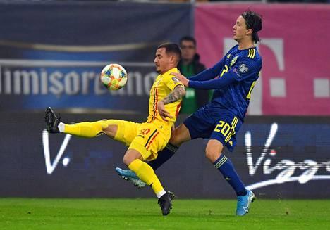 Romanian Ionut Mitrita kamppaili pallosta Ruotsin Kristoffer Olssonin kanssa.