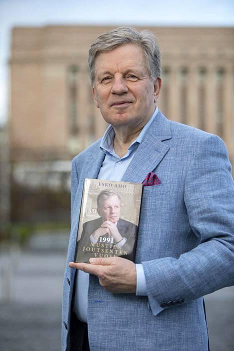 90-luvun porvarihallituksen pääministeri Esko Aho (kesk) lupaa lähettää Maria Ohisalolle (vihr) tuoreen kirjansa, jossa kerrotaan 1990-luvun alun karmeasta taloustilanteesta.