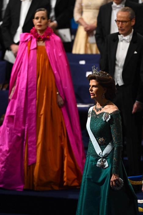 Silvia oli valinnut ylleen tummanpuhuvan, vihreän iltapuvun, joka jätti hänen olkansa paljaiksi. Asun täydensivät tiara ja suuri kaulakoru.