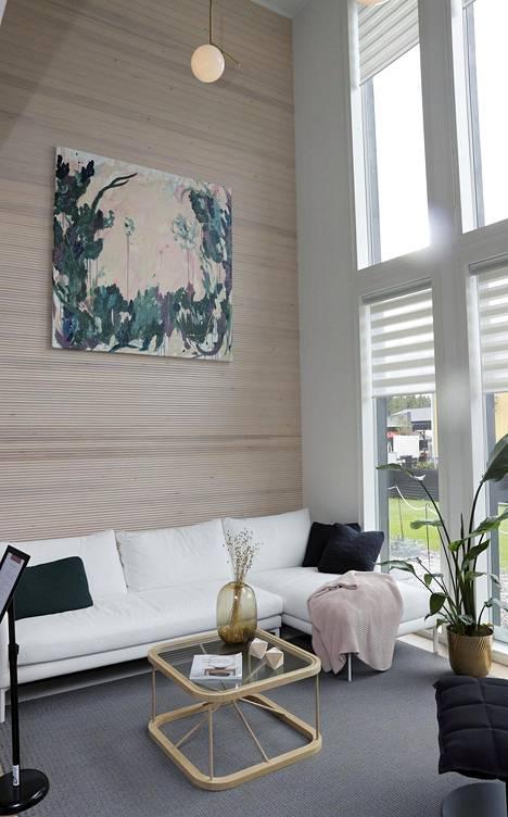 Messukohteesta 8, Dekotalo Ruuti, löytyy puupaneloitu olohuoneen seinä. Huonekorkeus on ajankohtaiseen tyyliin huima. Isot ikkunat tuovat valoa suhteellisen pieneen olohuonenurkkaukseen.
