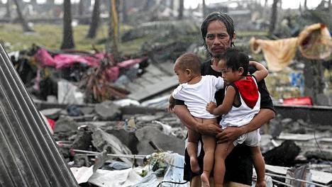 Isä odottaa lapsineen ruokajakelua väliaikaisen suojan luona Taclobanissa.