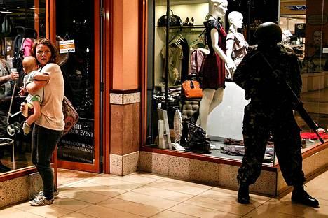 Nainen suojasi lastaan ostoskeskuksen luona.