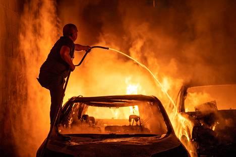 Mies yritti sammuttaa palavaa autoa Minneapolisissa perjantaina.