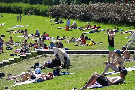 Ihmiset ottivat aurinkoa Vetokannaksen uimarannalla Vantaalla tiistaina.