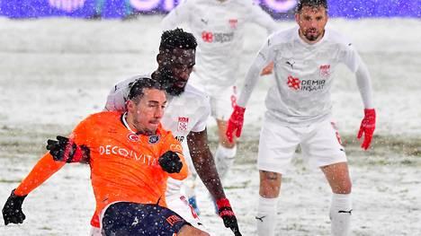 Basaksehirin Enzo Crivelli (edessä) ja Sivassporin Aaron Appindangoye taistelivat pallosta lumisessa Istanbulissa.