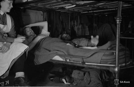 """Uskollinen sairaalan kissa """"""""Otto Kuusinen"""""""" hoitaa reumatismipotilasta. Valkjärvi 1941.10.24"""