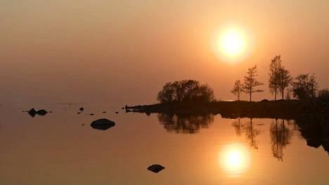 Aurinko laskee arkistokuvassa lämpimän ja kirkkaan päivän päätteeksi Selkämerellä Eurajoen Kuivalahdesta kuvattuna.