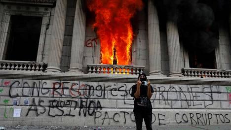 Kansainvälisiä sormimerkkejä näyttänyt mielenosoittaja poseerasi tuleen sytytetyn kongressirakennuksen edustalla Guatemala Cityssa lauantaina.