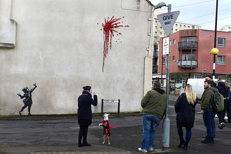 Ihmiset kerääntyivät ihastelemaan mysteeristä taideteosta.