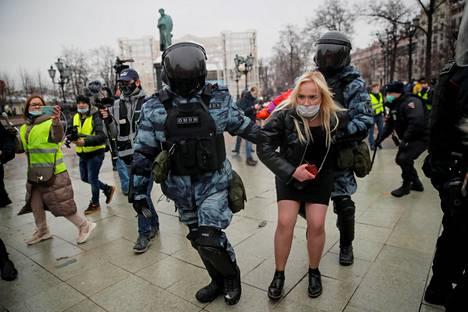Poliisit kuljettavat mielenosoittajaa.