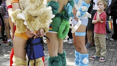 Poika katseli uteliaana Sateenkaari-paraatin osanottajia Tokiossa. Tuhannet seksuaalivähemmistöihin kuuluvat marssivat kaupungissa syrjinnän vähentämiseksi.