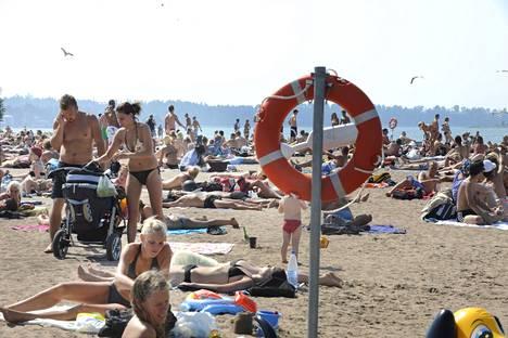 Auringon ja meren palvojat ovat pakkautuneet Hietaniemen rannalla kesäkuun hellepäivinä.
