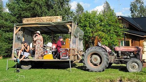Soittajat ja laulajat kiertävät Mallusjärven vanhan Massey Ferguson -traktorin lavalla. Kuva kesältä 2012.