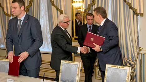 Presidentti Viktor Janukovitsh (oik). puristi Saksan ulkoministerin Frank-Walter Steinmeierin kättä perjantaina. Neuvotteluissa oli mukana myös Vitali Klitshko (vas.).