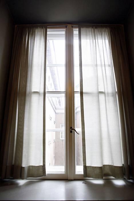 Varjosta auringonpuoleiset ikkunat vaaleilla verhoilla.