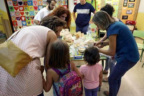 Oppilaat ja vanhemmat laittoivat ruokaa koulurakennuksessa, jossa perheet aikovat viettää yönsä.
