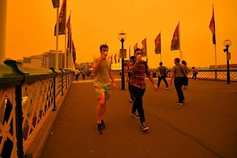 Sydneyn keskustassa perjantaina kulkeneet suojautuivat hengityssuojaimin savulta.