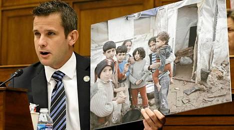 Republikaanien edustaja Adam Kinzinger pitelee kuvaa Syyrian lapsista senaatin valiokunnan kuulemisessa.