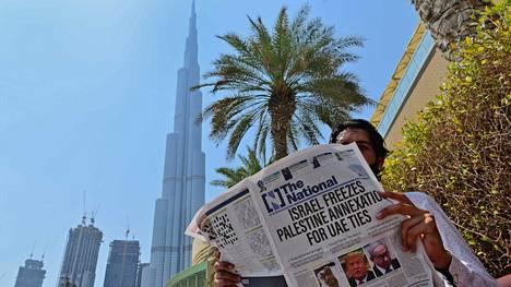 Mies luki paikallista sanomalehteä Dubaissa perjantaina.