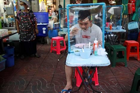 Mies ruokaili koronaturvallisesti bangkokilaisessa katukeittiössä huhtikuun lopulla.