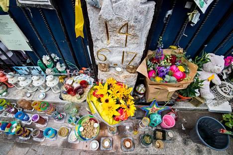 Ihmiset toivat kukkia ja kynttilöitä Grenfell- tornitalon edustalle tragediaa seuranneena päivänä.