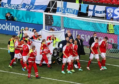 Tanskan pelaajat muodostivat ringin Eriksenin ympärille, kun tätä elvytettiin ja saattoivat paareilla makaavaa ystäväänsä ambulanssille päin.