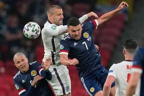 Skotlanti otti Englannin vieraana tasapelin. Kuvassa Skotlannin Lyndon Dykes (vas.) ja John McGinn taistelevat pääpallosta Englannin Luke Shaw'ta vastaan.