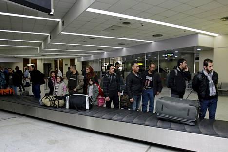 Irakilaispakolaiset kuvattiin odottamassa laukkujaan lentokentällä Bagdadissa. He olivat palanneet kotimaahansa Suomesta.