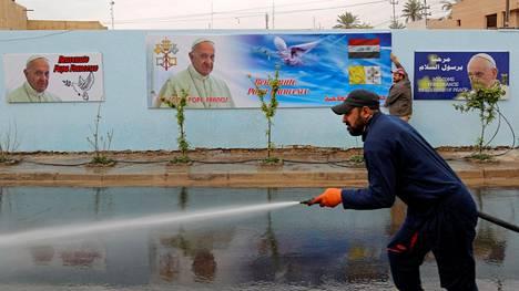 Mies puhdistaa katua bagdadilaisen katedraalin edustalla ennen paavin vierailua.