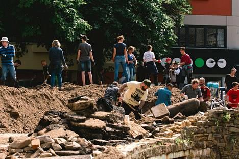 Ihmiset raivasivat tulvan tuhoamaan tietä Bad Münstereifelissä Saksassa.