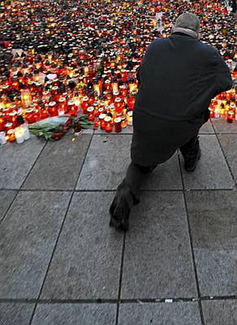 Mies polvistui rukoilemaan kynttilämeren ääreen.