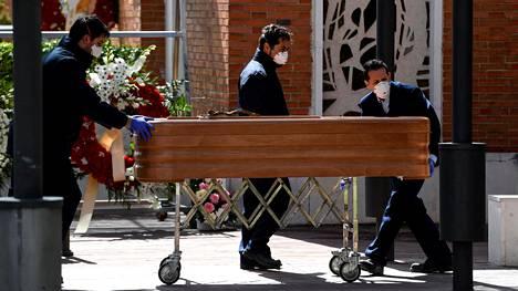 Kasvomaskein suojautuneet ruumishuoneen työntekijät siirsivät koronavirukseen menehtyneen arkkua hautausmaan krematorioon Madridissa tiistaina.