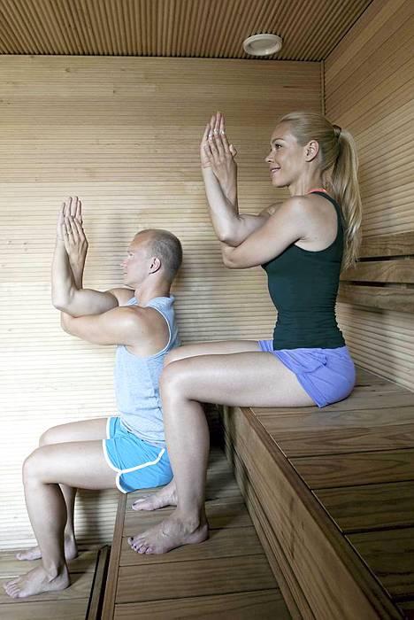 2. Saunakotka. Alkuasento: käy istumaan lauteiden etuosaan, laita jalat lantion levyiseen haaraan, tuo nilkat polvien alapuolelle ja käännä jalkaterät suoraan eteenpäin. Paina hieman molempia istuinluita lauteisiin, ojenna selkä suoraksi ja jännitä kevyesti vatsalihaksia. Nosta kädet ylävartalon eteen, niin että kyynärpäät ovat rinnan alapuolella ja sormet osoittavat kattoon. Tuo oikea käsi alimmaiseksi ja laita kämmenet vastakkain tai ota oikealla kädellä vasemman käden kiinni peukalosta tai ranteesta. Mikäli et saa käsiä näin, laita kämmenselät vastakkain. Tee näin: hengitä sisään, ojenna selkä pitkäksi, nosta kyynärpäitä ylöspäin ja käännä katse sormenpäihin. Hengitä ulos, tuo kyynärpäät kiinni rintaan, laske leuka rintaan ja pyöristä yläselkää. Anna tasaisen hengityksen ohjata käsien liikettä ylös ja alas sekä katseen nousta ja laskea liikkeen mukana. Kesto: tee liike 3-5 kertaa siten, että oikea käsi on alimpana ja toista sama vasen käsi alimpana. Vaikutus: liike venyttää hartiaseudun lihaksia ja lisää rintarangan liikkuvuutta.