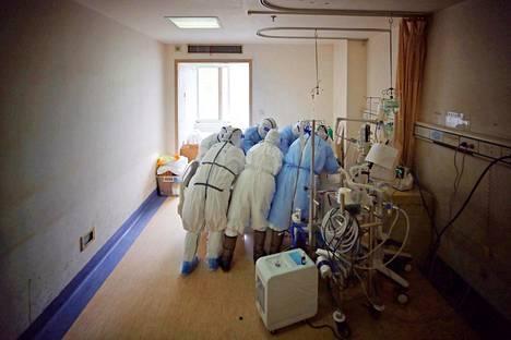 Korona hallinnassa. Lääkintähenkilöstö hoiti koronapotilasta Punaisen ristin sairaalassa Kiinan Wuhanissa keskiviikkona. Kiinassa potilasmäärät ovat laskeneet.