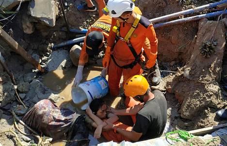 Pelastajat auttoivat talon raunioihin jäänyttä ihmistä Palussa Indonesiassa sunnuntaina.