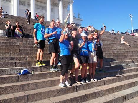 Juoksijat juhlistivat urakan päättymistä Helsingin Tuomiokirkon portailla.