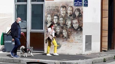Katutaiteilija Christian Guemy on maalannut terrori-iskun uhrien muistoksi muraalin Charlie Hebdon entisen toimituksen läheisyyteen.