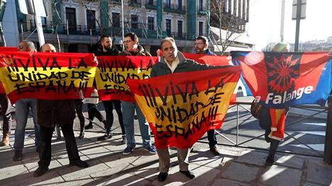 Eläköön Espanjan yhtenäisyys, lukee korkeimman oikeuden edustalle kokoontuneiden mielenosoittajien lipuissa. Taustalla näkyy myös Francon diktatuurin aikana hallinneiden falangistien tunnus.