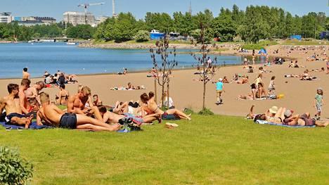 Ihmiset nauttivat auringosta Helsingin Hietaniemessä kesällä 2016.