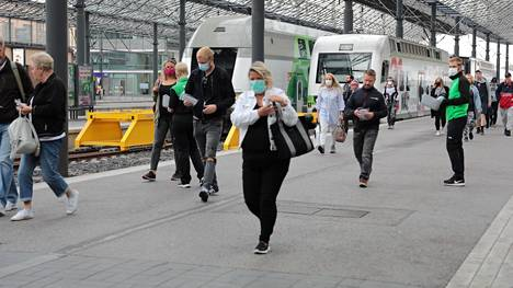 Useat ihmiset käyttivät kasvomaskia Helsingin päärautatieaseman junalaiturilla aamukahdeksan jälkeen perjantaina.