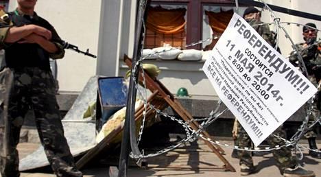 Aseistetut miehet vartioivat viikonloppuna hallintorakennuksia Luhanskissa. Julisteessa mainostettiin sunnuntain kansanäänestystä.