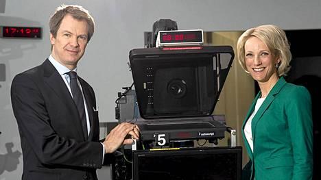 Peter Nyman ja Maija Lehmusvirta viestittelevät edellisenä päivänä, minkä väriset vaatteet aikovat laittaa uutislähetykseen.
