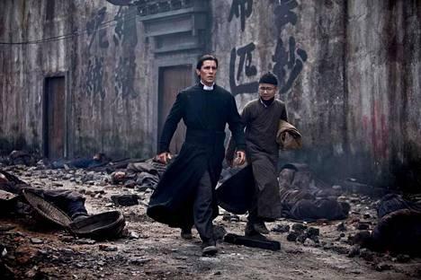 Christian Bale suojelee naisia kirkossa.