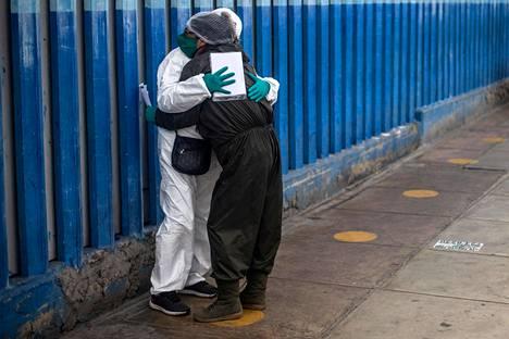 Nainen suree koronaviruksen aiheuttamaan tautiin kuollutta miestään Alberto Sabogalin sairaalassa Limassa.