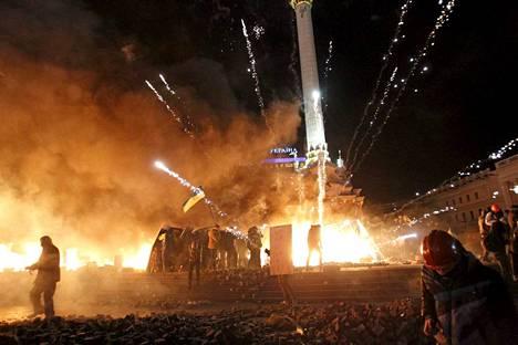 Liekkejä ja ilotulitteiden räjähdyksiä Itsenäisyyden aukiolla Kiovassa.