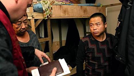 Maahanmuuttoviranomainen tarkistaa kiinalaisten papereita motellissa Moskovassa. Venäjän viranomaiset pyrkivät torjumaan laittoman maahanmuuton.