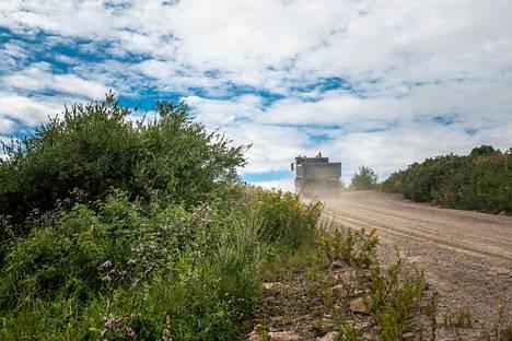 Kuorma-auto huristaa pitkin täyttömällä kulkevaa hiekkatietä.
