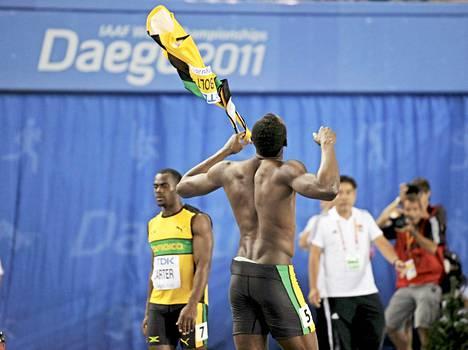 Usain Bolt repi paitansa otettuaan varaslähdön Daegun MM-finaalissa 2011.