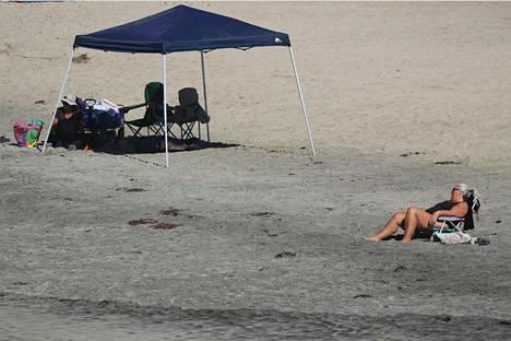 Nainen uskaltautui Kalifornian Oceansidessa hiekkarannalle kuumuudesta huolimatta.